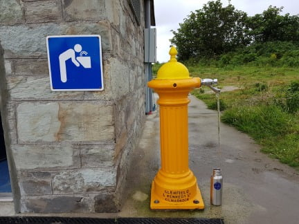 yellow water fountain for refilling water bottles in Rosscarbery Cork, Ireland